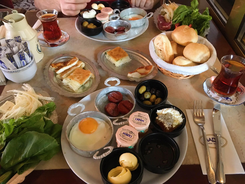 """Když už jsme u toho jídla. Básnila jsem vám o turecké snídani? Že ne? Ta z MADO je vynikající. Spousta sýrů, speciální """"klobása"""" sucuk, čerstvá zelenina, křupavé pečivo, čerstvý med, speciální marmelády a tvaroh, typický börek a samozřejmě spousta čaje. Mňam a mňam."""